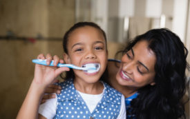 Young girl brushing teeth with mother by her side